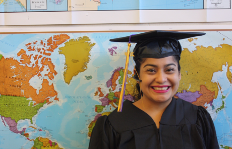 graduate smiling for picture with map of the world in the background
